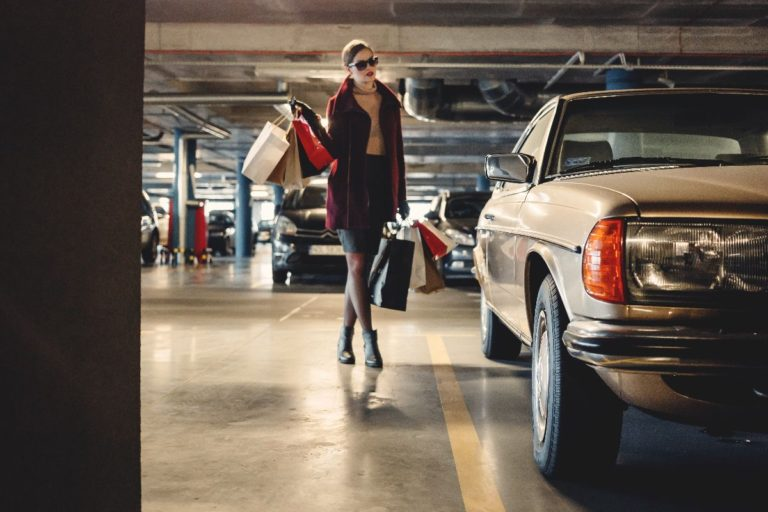 A lady standing with shopping bags next to a car